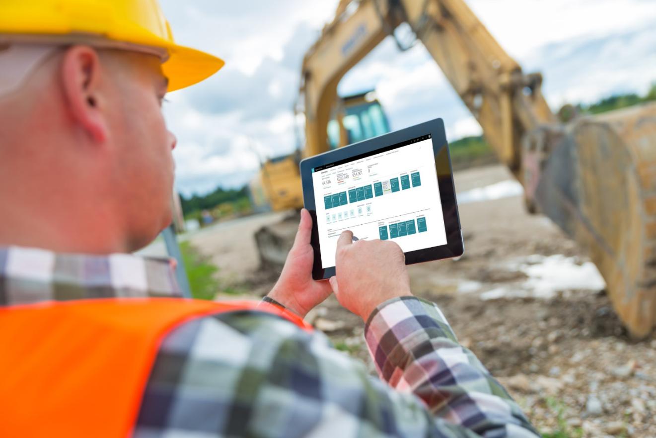 Man die op de bouwplaats data afleest van zijn tablet